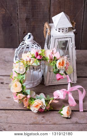 Flower wreath and decorative lanterns with candles on wooden background. Still life. Wedding inspiration. Selective focus.