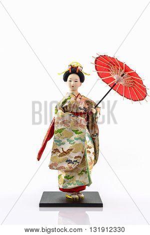 Japanese geisha dolls with japanese umbrella on white background.