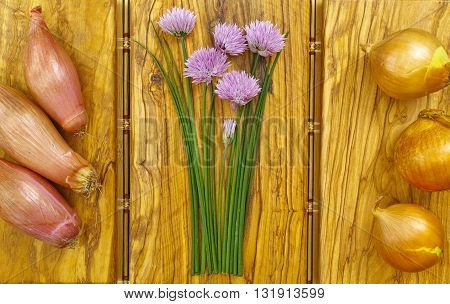 Fresh green blooming chives shallots and yellow onion on olive wood background