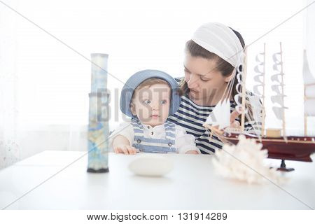 Mother And Her Baby Boy Playing With Model Of Ship.