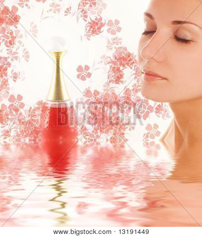 Beautiful girl's face and perfume phial in rendered water