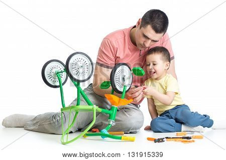kid boy and his father fixing children bike