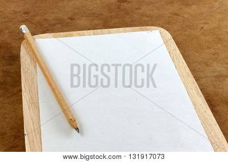 blank paper note and pencil on the wooden frame