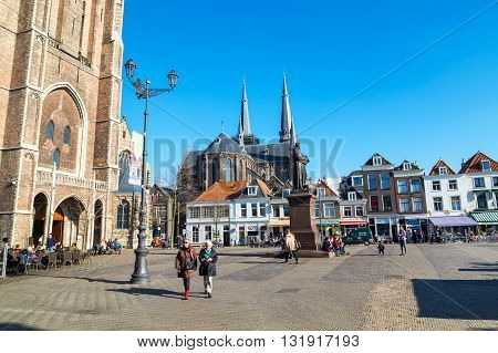 Delft, Netherlands - April 8, 2016: Colorful street view with traditional dutch houses on the square, church, people walking in downtown of popular Holland destination