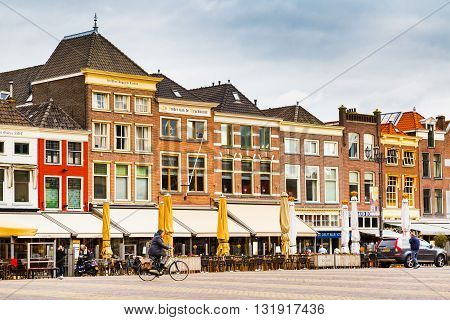 Delft, Netherlands - April 6, 2016: Colorful street view with traditional dutch houses on the square, bicycles, people walking in downtown of popular Holland destination
