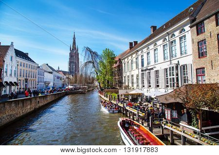 Bruges, Belgium - April 10, 2016: Scenic cityscape with medeivel houses, boat with tourists in Bruges, Belgium