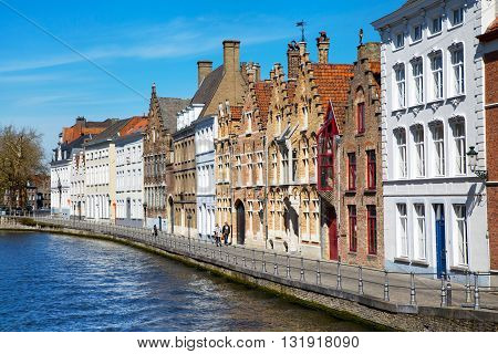 Bruges, Belgium - April 10, 2016: Panorama with canal and colorful traditional houses against blue sky in Brugge, Belguim