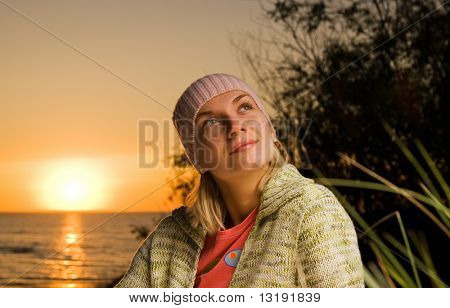 Beautiful young girl on the beach at sunset time