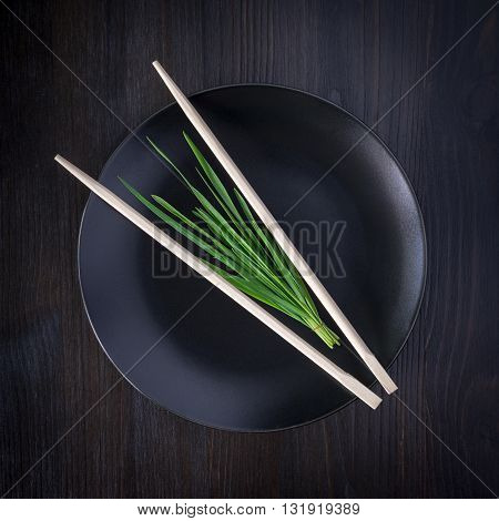 bunch of fresh herbs on an empty black plate with chopsticks