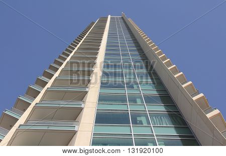 Bottom up view of a high office building with balcony and windows
