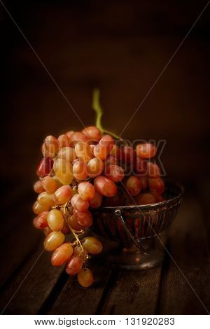 Fresh grapes in small metal vase on wooded background vertical composition