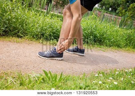 Twisted ankle - running sport injury. Male athlete runner touching foot in pain due to sprained ankle.
