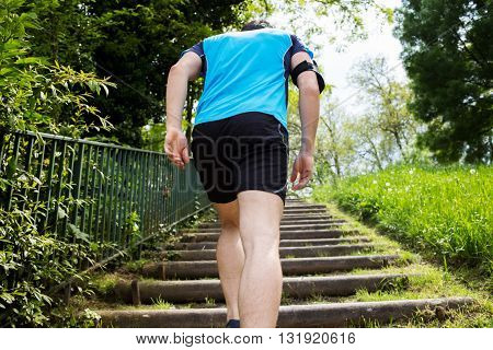 Close up of young man back running up the stairs in a city park.Runner man Practice training on stairs in a city park.