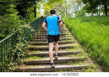 Close up of young man running up the stairs in a city park.Runner man Practice training on stairs in a city park.