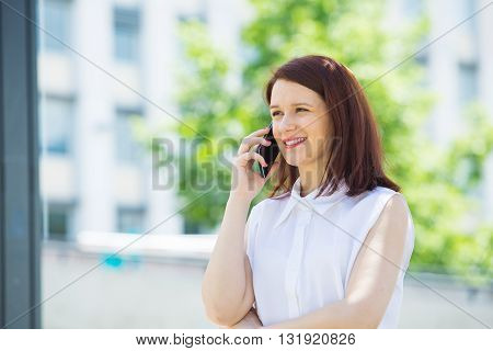 Smiling young girl talking on mobile phone in a city .Young smiling student girl outdoors talking on cell smart phone.Life style.City