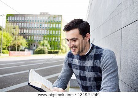 University.Smiling young student man holding and reading book in campus .Young smiling student outdoors Life style.City.Student.