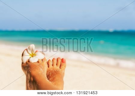 Holiday concept. Woman feet with frangipani flower relaxing on beach enjoying sun and splendid view