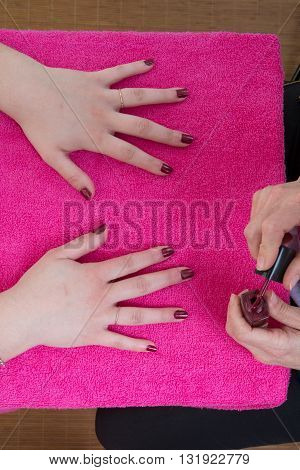 Girl In A Nail Salon Receiving A Manicure By Beautician