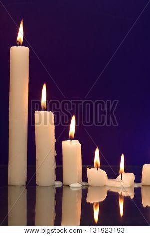 Set of lighting candles in a row on nice dark background