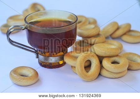 Yellow bagels and cups of black tea. Still-life with scattered bagels and teacups