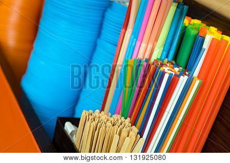 Multicolored vivid plastic drinking straws and plastic caps at the cafe