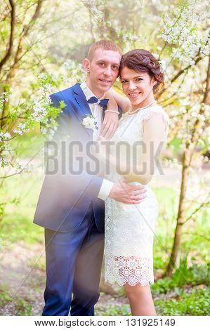 Wedding smiling Couple. White flowers in the park