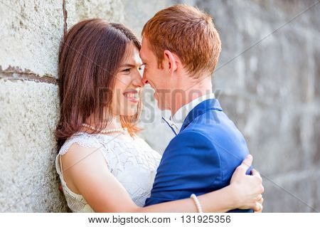 Young couple smiling while leaning on an old textured wall