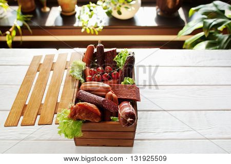 Assortment of sausages in little wooden box on white wooden table. Open box with variety of sausage. Copyspace, blured background.
