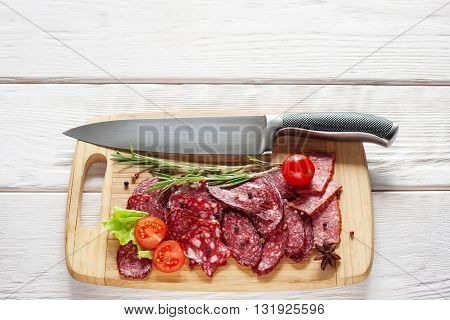 Sliced salami and knife on wooden cutting board on white wooden background. Close-up of knife and salami on cutting board. Horizontal position. Flat lay of sliced salami mix. Free space for text