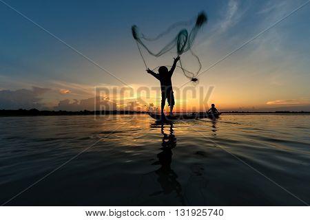 Fisherman throwing net on boat fishing at lake