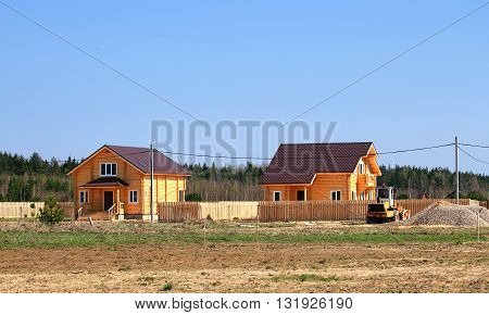 Construction of wooden cottages at the edge of forest
