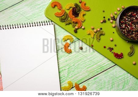 White notebook with spices and noodles on green wooden background. Close up culinary ingredients