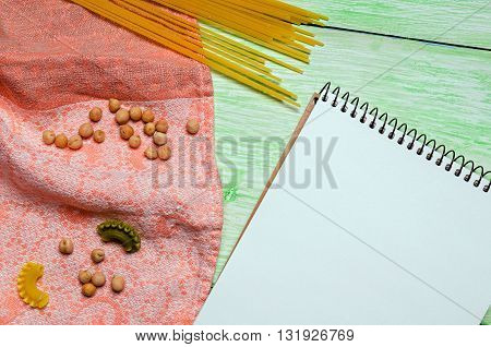 White notebook with spices and noodles on green wooden background. cookbook on the table