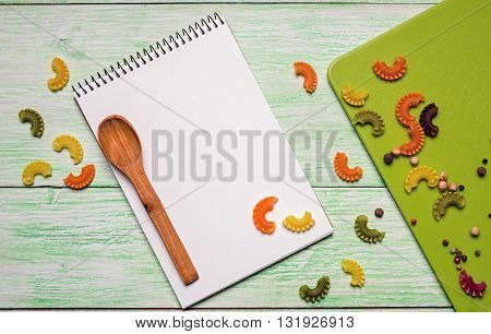 White notebook with spices and noodles on green wooden background. cookbook and spoon on the table