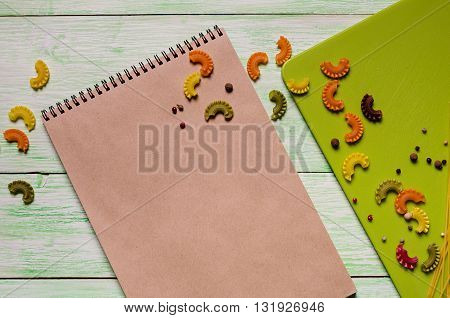 brown notebook with spices and noodles on green wooden background. Close up culinary ingredients