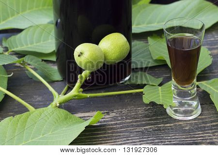 Liqueur with green walnuts on a dark wooden background