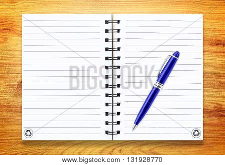 Note book with pen on wood background