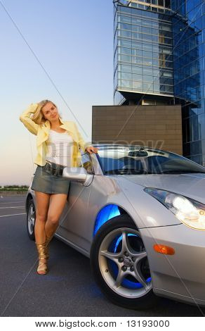 Sexy blond girl stands near modern sport car