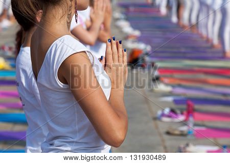 A group of unrecognizable women practicing yoga outdoors