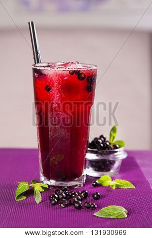 red currant fresh cold tea in tall glass on violet background