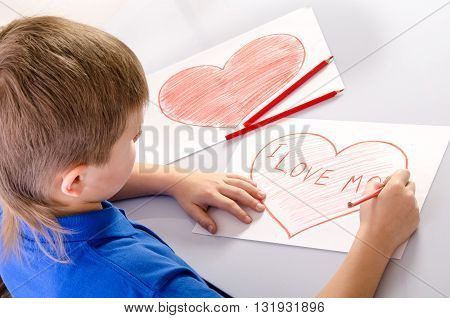 childs hand drawing a heart that says I love mom