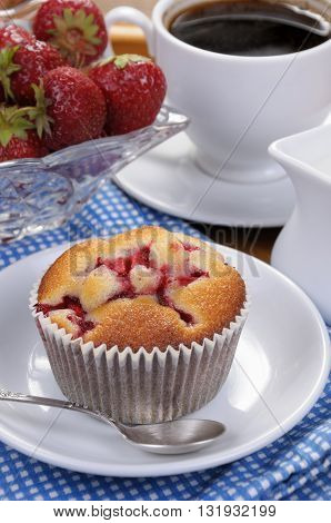 Muffin filled with strawberries on a table cup of coffee
