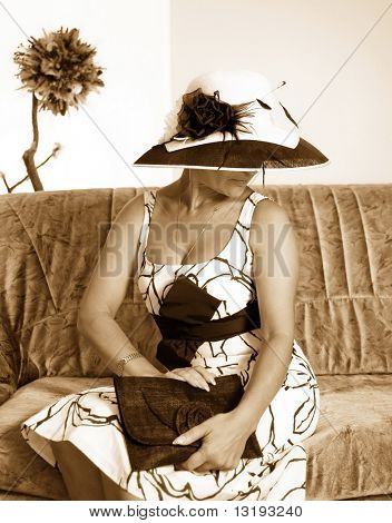 Sepia toned picture of a woman with a hat sitting on a sofa