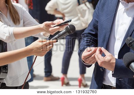 Reporters making interview with businessman or politician. Press conference.