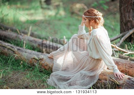 Beautiful Artistic Photo Ginger Girl In White Dress Sitting On A Tree In The Woods.