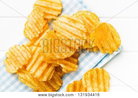 Crinkle cut potato chips on table. Tasty spicy potato chips. Top view.