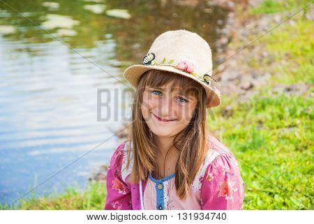 Portrait of a smiling cute girl in a straw hat