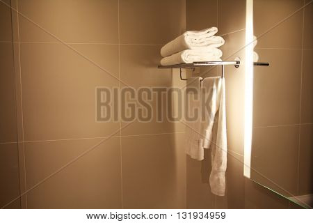 Hotel bathroom with clean white towels and copy space to be used as a background