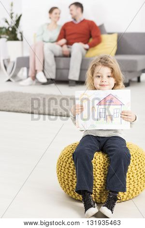Picture of a cheerful little girl sitting on a yellow tuffet holding a drawing of a house and her happy parents in the blurred background