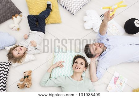 Shot of a young family with a child lying on the floor among cushions and mascots seen from above